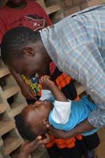 Blaise, 6 months old, with a UNICEF caregiver at the Early-Childhood Development Centre during a baseline survey in Rwamagana.  ©Jung Park – UNICEF Rwanda
